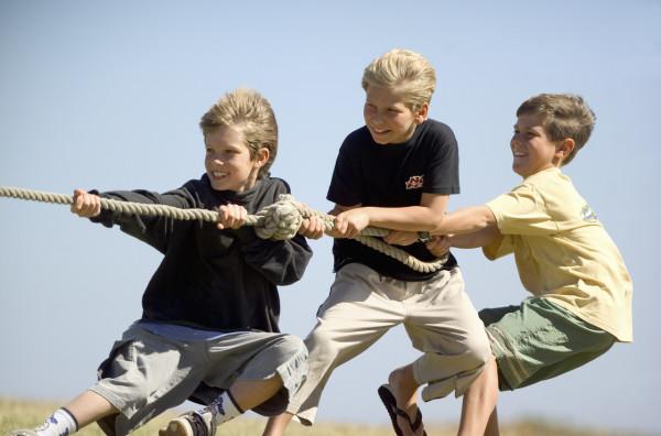 Three boys playing tug-of-war